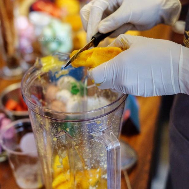 Memotong dan memasukan buah mangga kedalam blender